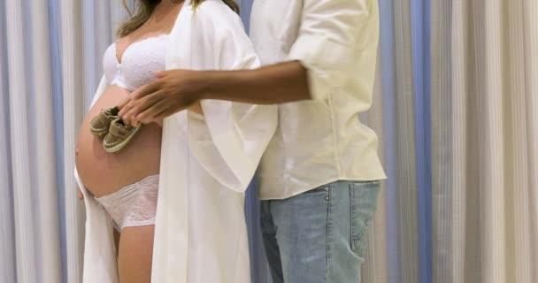 Těhotná ve spodním prádle předvádí své břicho a manžel drží malé dětské boty.