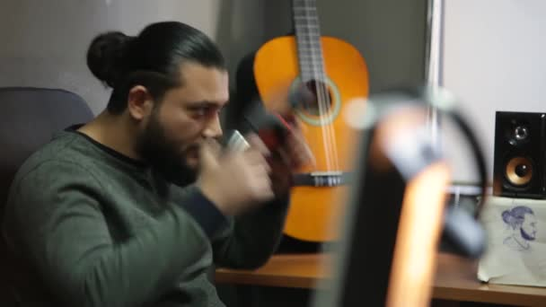 Young man wearing wireless headphones chilling listening to music sit on studio, happy relaxed guy enjoying lounge sound with guitar background in peaceful mood feeling