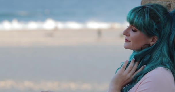 Alluring blue hair young woman, wall, beach, copy space - SLOMO