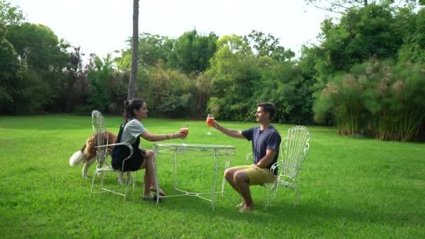Junges Paar trinkt einen Daiquiri im grünen Hinterhof