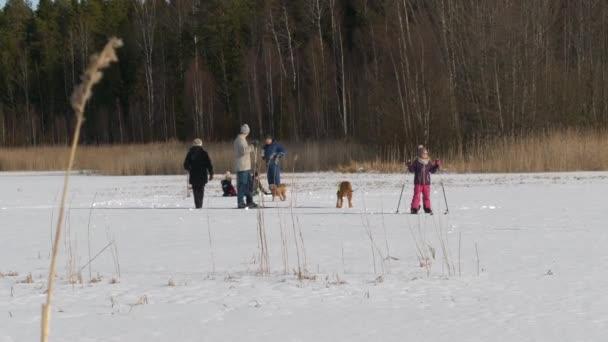 Multigenerační rodina těší zimní aktivity, slunečný den na zasněženém zamrzlém jezeře