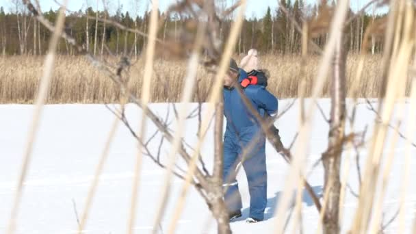 Elderly Man Carrying A Girl on his back in deserted winter scenery, slow motion