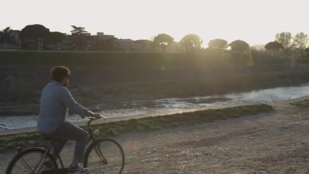Back and wide shot of a young man who is riding bicycle on background city lake in Florence, Italy. Concept of relax, enjoying the nature. Man going to work in bike, green solution.