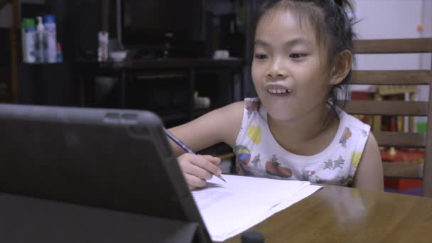 A little child girl studies e-learning from school at home, using tablet to learn academic lessons online. View behind tablet to see the girl. 6-7 years old student.