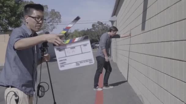 Boy man asian claps slate clapper for filming in street with angry man