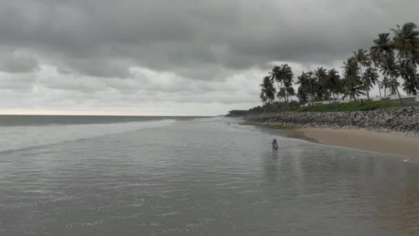 4k Drohnenaufnahme einer hübschen 27-jährigen Inderin, die ihren friedlichen Spaziergang am Strand genießt, vor dem Hintergrund regnerischer Wolken entlang der Küste von Varkala