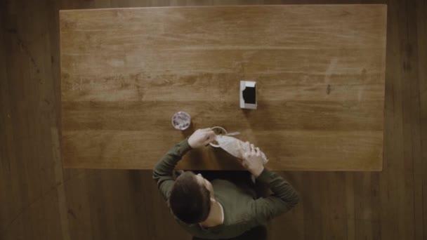 Muž připravuje své obiloviny a jogurt na snídani na stole - Top View Shot