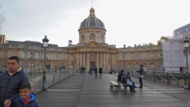 Institut de France (Institute of France) Viewed From Pont des Arts Bridge With People Walking And Sitting On The Wooden Bench At Daytime In Paris, France. - static shot