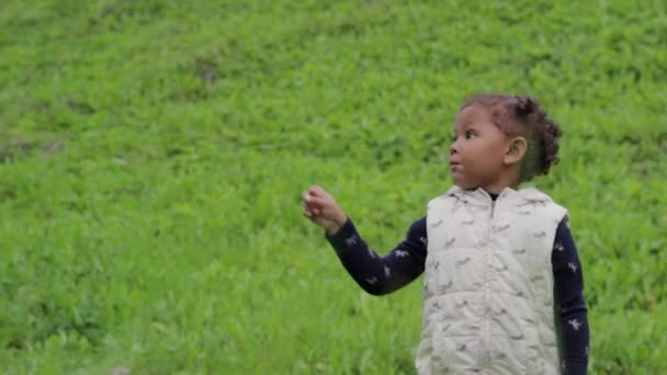 Little black girl learning directions with her mother outdoors