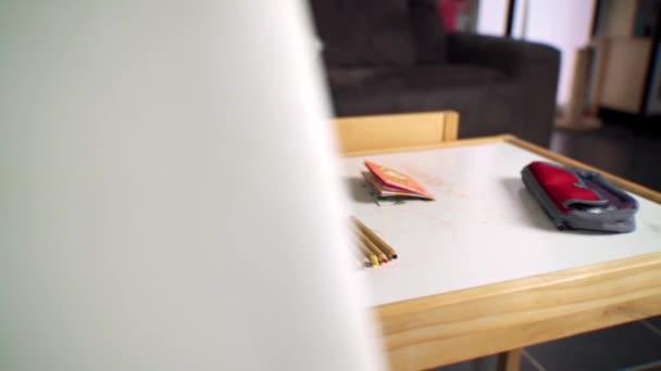 Rychlost ramp pan záběr omalovánky a pera na stole v dětském pokoji.