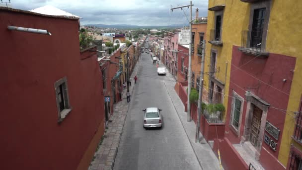 A street in San Miguel de Allende, Guanajuato Mexico with yellow and red houses, some cars and people