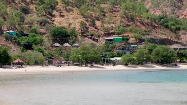 Traditional Timorese houses in the hills and children playing in the sea on stunning white sand beach tropical island coastline in Dili, Timor Leste, Southeast Asia
