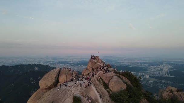 Tourists climb Bukhansan mountain with a beautiful sunset view of Seoul