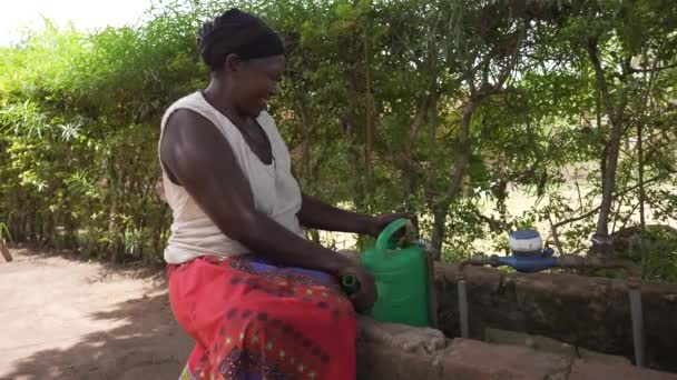 Local African woman doing housework and smiling in a rural village of Uganda. Filling water in the watering can. Africa 4K.