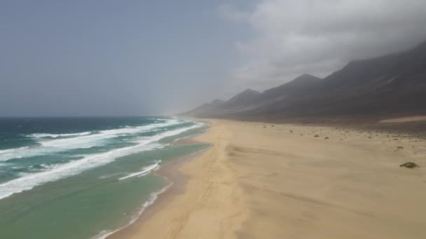 aerial drone shot of big waves crashing on the long white beach of cofete with beautiful mountains in the background in Fuerteventura, canary island.