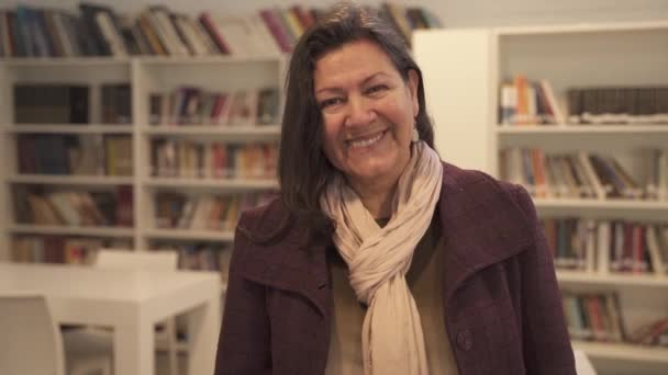 Pretty brunette middle aged woman smiling at camera standing inside library,close up