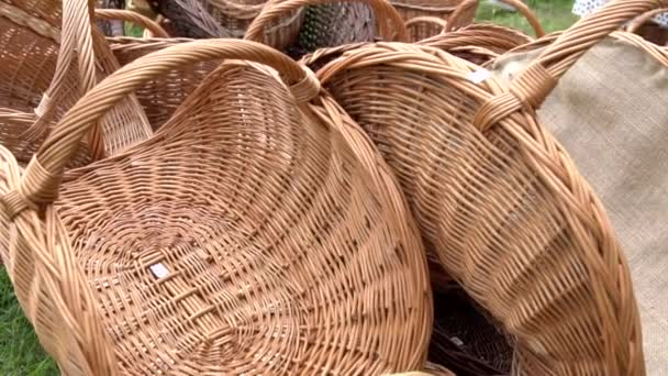 Collection of wicker baskets selling on the market. Empty wicker picnic baskets, Easter holiday containers stacked on the meadow. Collection of brown handmade rattan basket.