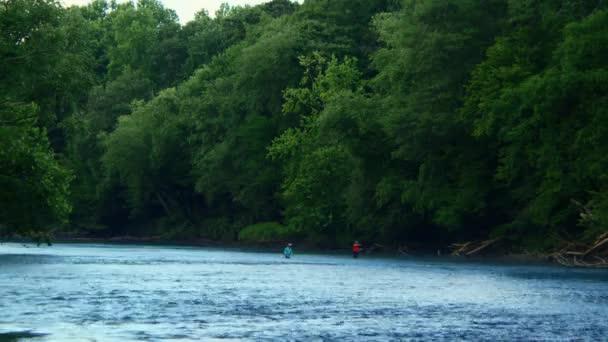 Dva lidé rybaří po řece.