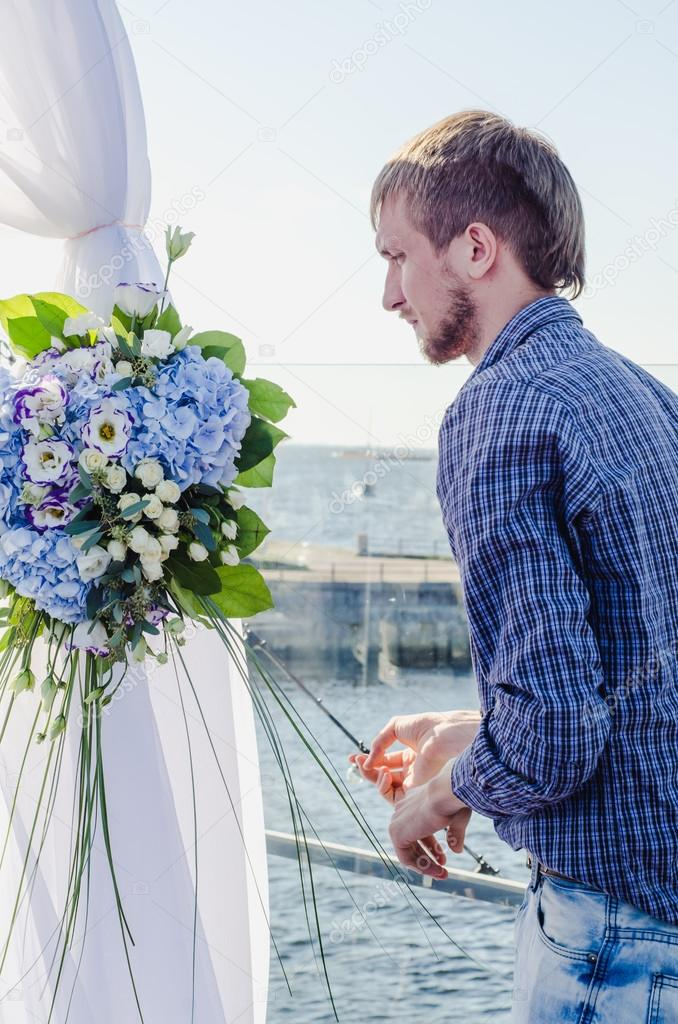 Professional florist at work: young handsome male making fashion modern composition bouquet of blue and white different flowers. Floral Design. Job concept serious bearded man working outdoors summer