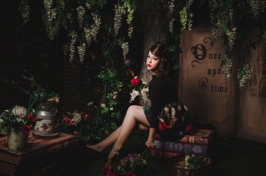 Magic portrait of romantic beautiful girl with wavy hair, red lips, art dress, holding rose flower, sitting on books. Female in scenery of Alice in Wonderland. Fashion fairy tale about princess, walki