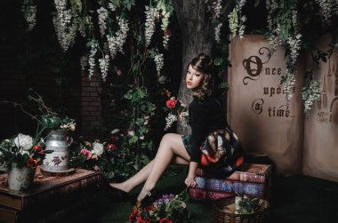 Magic portrait of romantic beautiful girl with wavy hair, red lips, art dress, holding rose flower, sitting on books. Female in scenery  Alice in Wonderland. Fashion fairy tale about princess, walking