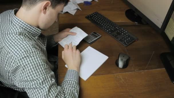 Člověk píše s kontroly plateb do poznámkového bloku