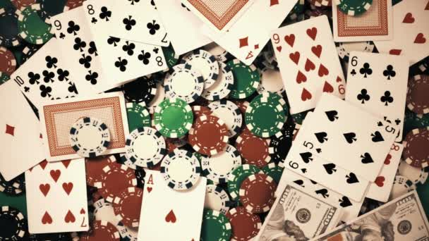 Účty padají na stůl s pokerovými žetony a hracími kartami ve zpomaleném filmu