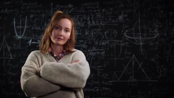 Portrait of young female student stands in front of blackboard with mathematics formulas