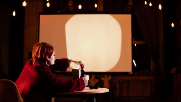 Dame im Sessel in gemütlichem Raum legt Fotonegative in Diaprojektor ein, um sie zu zeigen