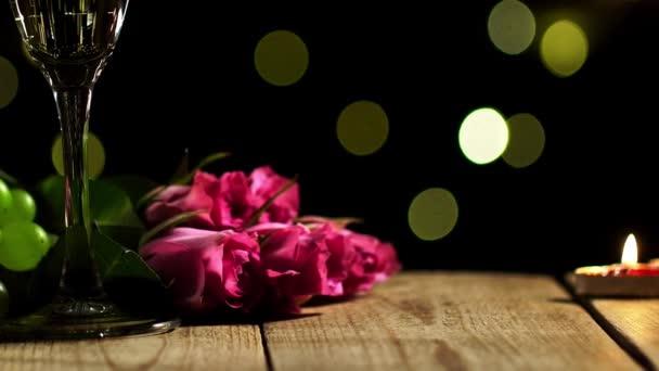 Detailní záběr romantického překvapení z servírovaného stolu s sklenicemi plnými šampaňského a růží