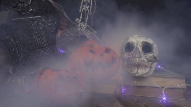 Kouř fouká na lebku a halloween dýně stojící v knihách