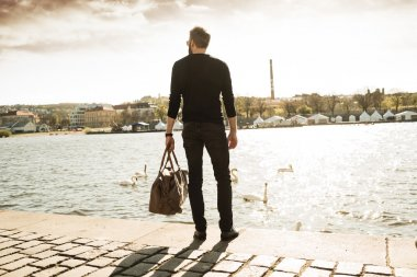 Young stylish man with his bag is standing in front of river
