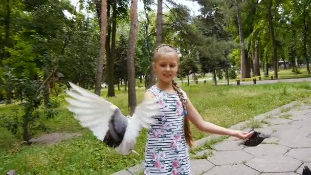 Girl playing with street pigeons