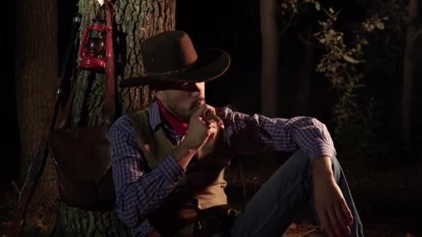 Kovboj s doutníkem v lese v noci