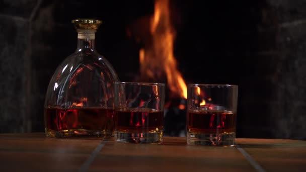 Palack és pohár whiskey-vel vagy konyakkal a kandallóban a tűz hátterében