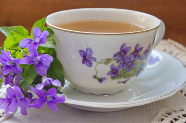 Vintage tea cup with motive of violets with violet flowers