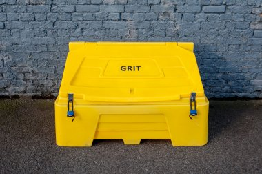 Grit bin against a brick wall