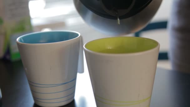 woman pouring steaming hot coffee into two mugs