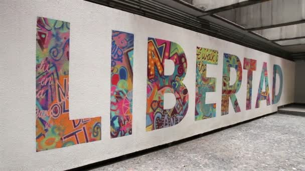 FULL SHOT. Word Libertad (freedom) painted in a wall.