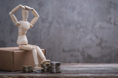 Small wooden dummy with sitting with coins over the grey concrete wall