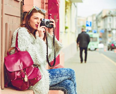 female photographer with professional SLR camera, natural light, selective focus on nearest part of lens with blend