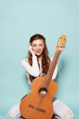 smiling beautiful young girl posing with guitar