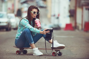 Beautiful young woman posing with a skateboard seat on skate, street fashion lifestyle. Keep cocktail and make selfie photo stock vector