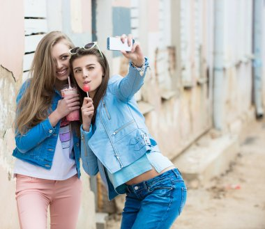 Hipster girlfriends taking a selfie in urban city context - Concept of friendship and fun with new trends and technology - Best friends eternalizing the moment with modern smartphone