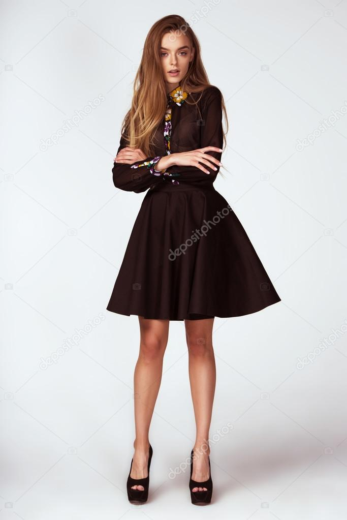 Fashion model woman pose in studio on gray background