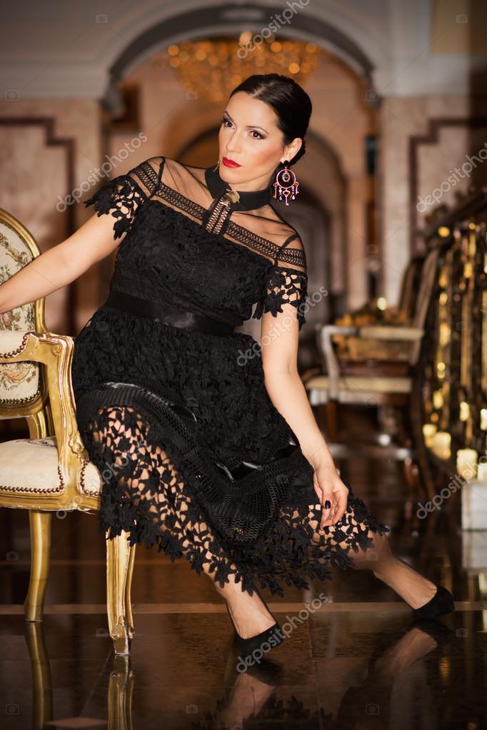 15625880747a Bella e attraente donna in abito da sera nero che posa in interni ben  decorati di un hotel Leopold I