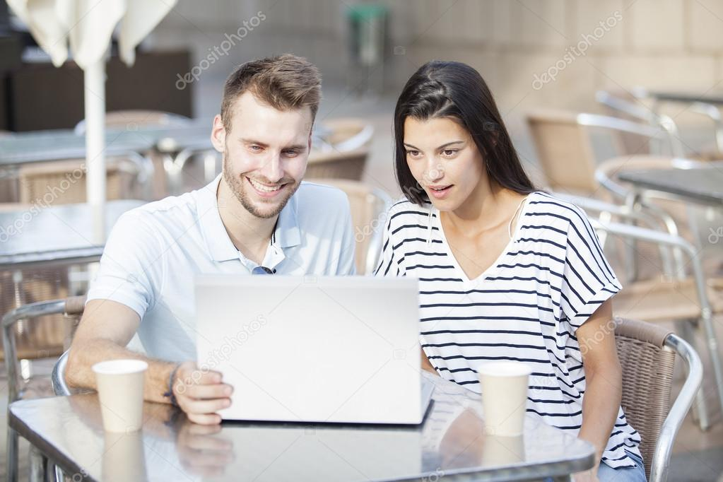 Happy couple watching social media in a laptop in a restaurant terrace