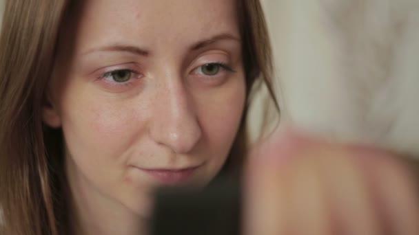 Junge Frau mit Handy zu Hause