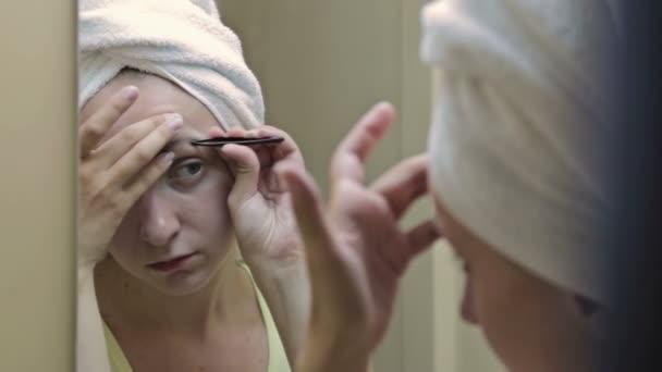 Krásná žena, škubání obočí před zrcadlem