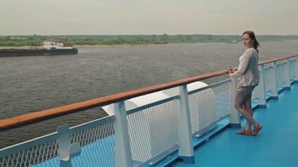 Mladá krásná žena stojící na palubě výletní lodi a při pohledu na řece